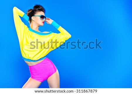 Shutterstock Glamorous fashion model posing in vivid colourful clothes and sunglasses. Bright fashion. Optics, eyewear. Studio shot.