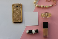 Glamorous female beauty accessories: perfume, bracelet, foundation, beads, phone in a gold case. Place for text. Selective focus. View from above. Gift. Layout, flat lay for beauty blog.