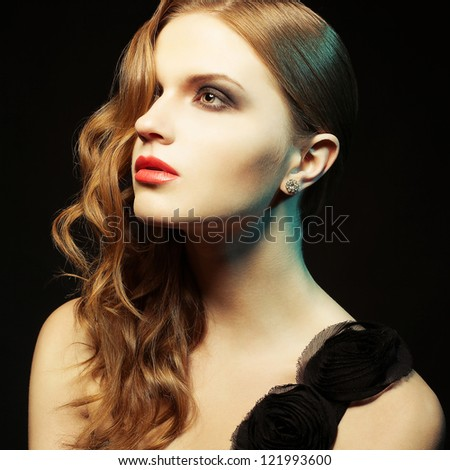Glamorous ginger girl with perfect makeup posing in black dress over black background. studio shot - stock photo