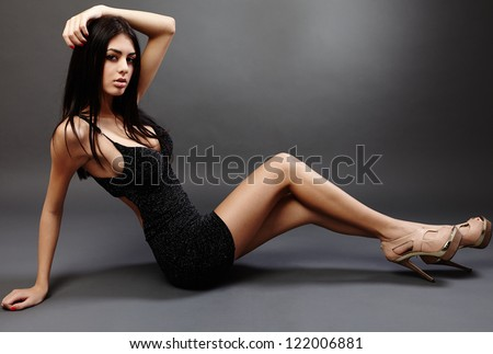 Glamorous hispanic young woman lying on the floor, studio portrait - stock photo