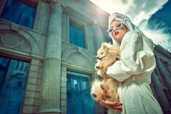 Glamorous lady in a white bathrobe with a white towel on her head and elegant red sunglasses walks along the street of a big city with a small dog in her arms. Beauty, fashion.