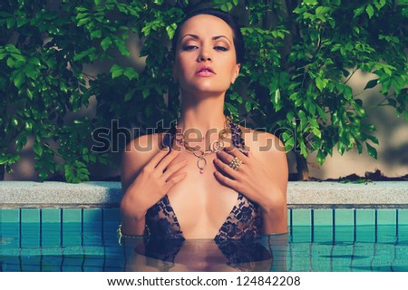 Glamorous lady in lace leotard on the side of the pool