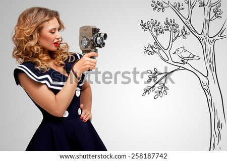 Glamorous pin-up sailor girl filming nature and wildlife with an old retro cinema 8 mm camera, standing in front of a bird on grey sketchy background. #258187742