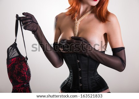 Glamorous pinup woman in corset holding red bra, studio shot on white background