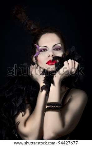 Glamorous pretty girl wearing black feather and intensive makeup. Black background. Studio shoot portrait/Glamorous Beauty