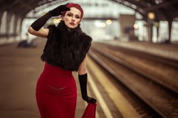 Glamorous retro girl at the train station in a red dress.Portrait of a beautiful girl. Vintage. Retro. Pin Up. Beautiful make-up and hairstyle in a classic style. Railway station.