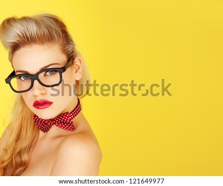 Glamorous retro model with an old-fashioned blonde coiffure, a polka dot bowtie and heavy rimmed glasses on a yellow studio background with copyspace