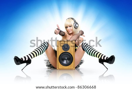 Glamorous sexy party girl in headphones with speaker, happy sound concept