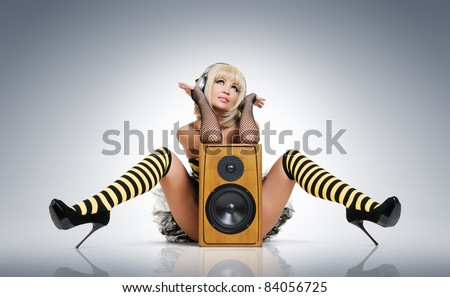 Glamorous sexy young girl in headphones with wooden speaker, sound concept