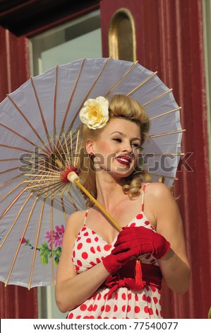 glamorous woman in 1940s fashion standing outside with an umbrella