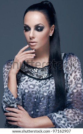 Glamorous woman on a grey background with glossy evening makeup
