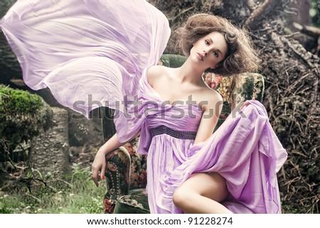 Glamorous woman sitting on a stylish chair