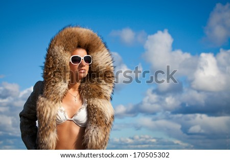 Glamorous woman with a sexy body wearing fur coat