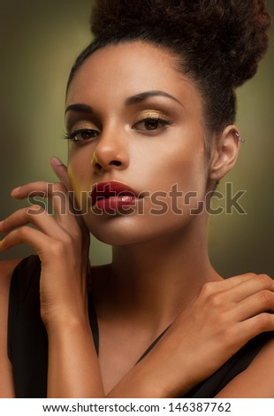 Glamorous young African woman gently touching her face.