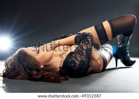 Stock Photo Glamorous young lying woman in black lingerie on black background