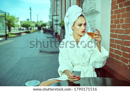 Photo of  Glamorous young woman in a white terry dressing gown with a white towel on her head sits at a table in a street cafe with a glass of wine and holding a phone in her hand. Fashion shot.