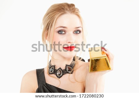 Glamorous young woman in black dress holding gold bar, portrait