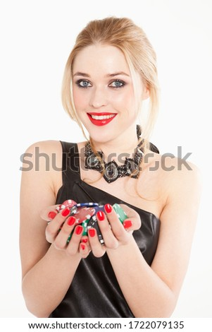 Glamorous young woman in black dress holding poker chips, portrait