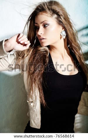 Glamorous young woman in near a wall