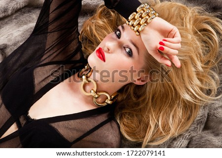 Glamorous young woman lying on bed, portrait