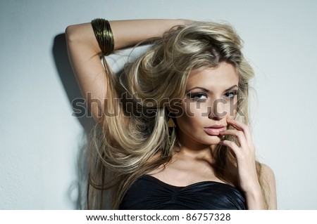 Glamorous young woman near white wall