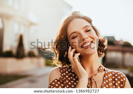 Glamorous young woman talking on phone with eyes closed. Outdoor photo of pretty caucasian girl with short brown hair.