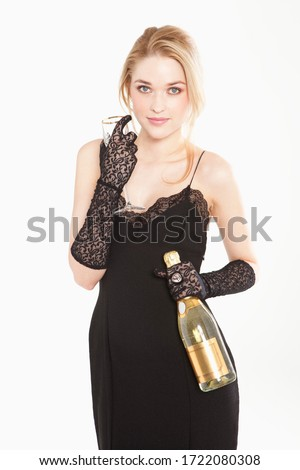 Glamorous young woman wearing black dress holding champagne, portrait