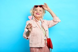 glamour awesome blonde senior lady taking off sunglasses, while eating lollipop. close up portrait. isolated blue background. beauty , happiness