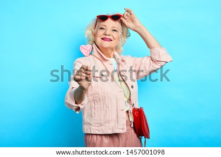 glamour awesome blonde senior lady taking off sunglasses, while eating lollipop. close up portrait. isolated blue background. beauty , happiness Сток-фото ©
