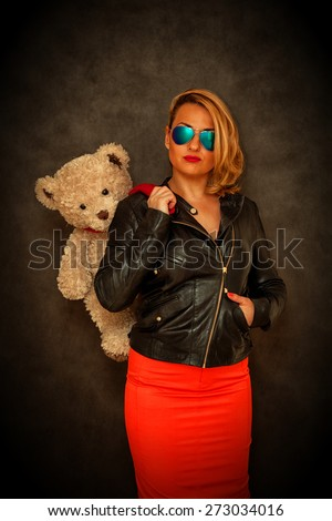 Glamour beautiful girl-blonde in a leather jacket, sunglasses and a red skirt with a teddy bear on a dark background