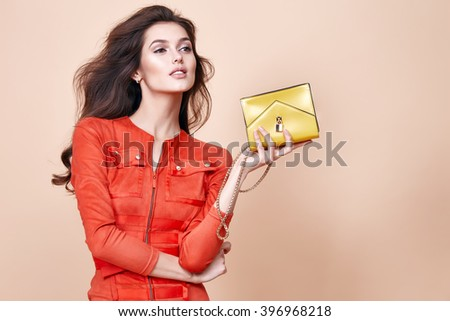 Glamour beautiful sexy brunette women, looks like a model, wearing evening make up in short red dress with small yellow bag in hands in fashion pose with amazing figure, perfect shape girl hairdo
