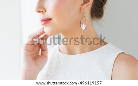 glamour, beauty, jewelry and luxury concept - close up of beautiful woman face with pearl earring