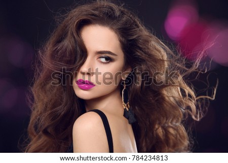 Glamour disco girl dancing. Beautiful girl with earring. Fashion portrait of gorgeous sexy brunette woman with long healthy hair style and evening makeup.