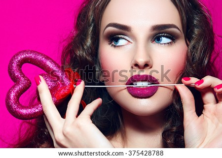 Glamour girl. The girl's face. Celebration. Heart in the hands. Pink make-up. Valentine Day. #375428788