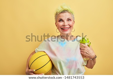 glamour kind of sport. gorgeous granny playing games with her grandsons, isolated yellow background, studio shot. #1481743553