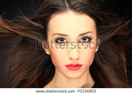 Glamour portrait of a woman on black with hair blowing with the wind