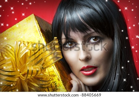 Glamour portrait of beauty woman with gold christmas gift box with ribbon on red background