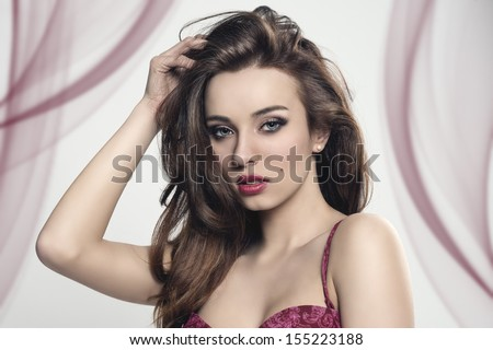 glamour portrait of brunette girl with long smooth hair, cute make-up and sensual eyes. Wearing red lingerie