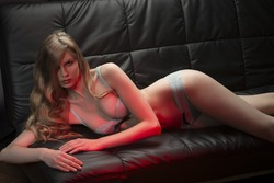 glamour portrait of cute woman with long blonde hair and sensual lingerie lying on black sofa in sexy pose