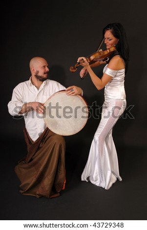 Glamour portrait of young sexy woman with a violin and exotic oriental drummer. black background