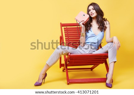 Shutterstock Glamour sexy girl clothes blue color silk blouse with lace beige cotton pants sit on chair  relax break hold trend bag stylish shoes beautiful face long brunette hair fashion collection model pose