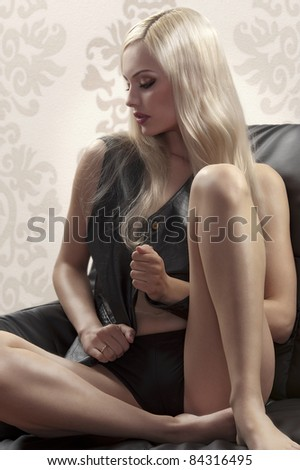 glamour shot of a blonde beauty sitting on a sofa wearing a black leather vest and panties