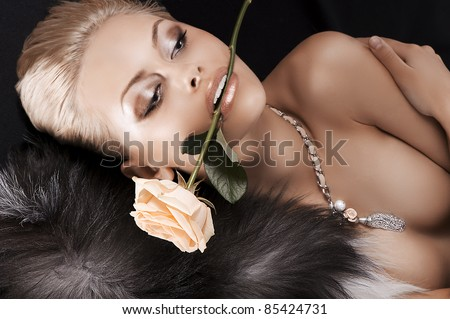 glamour shot of a sexy blonde laying on black wearing fur and a rose in her mouth