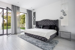 Glamour style gray bedroom interior with quilted headboard of the bed
