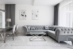 Glamour style living room with white walls and floor, gray quilted sofa, glass coffee table and glass dining table