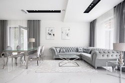 Glamour style white and gray living room with quilted corner sofa and elegant glass coffee and dining table