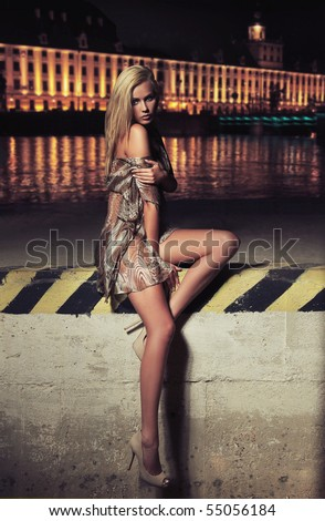 Glamour type photo of cute blonde sitting on the city bridge