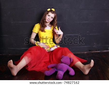 Glamour woman doll near black brick wall