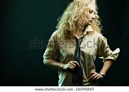 Glamour woman portrait in shirt holding her tie. Specific lighting.
