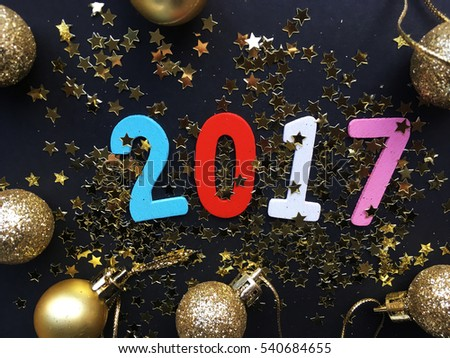 Glamour 2017. Wooden color 2017 date on black background with golden Christmas toys. New Year 2017. #540684655